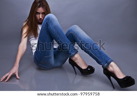 Young attractive woman siting on the studio floor. - stock photo
