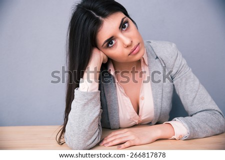 Young attractive woman sitting at the table over gray background. Looking at camera  - stock photo