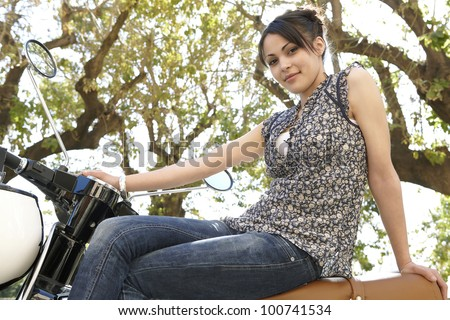 Young attractive woman sitting down on a motorbike with trees in the background, smiling at camera. - stock photo