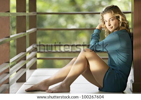 Young attractive woman sitting down on the floor of a balcony, smiling at camera. - stock photo