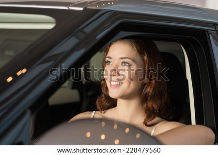 Young attractive woman sitting in new car - stock photo