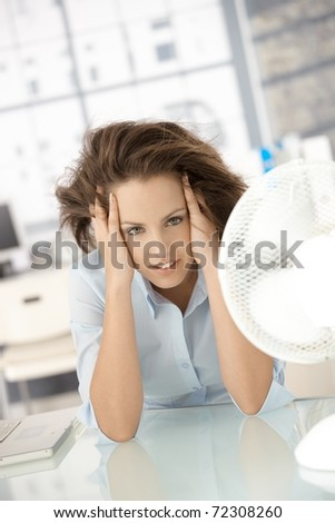 Young attractive woman sitting in office front of fan, feeling hot, cooling herself.? - stock photo