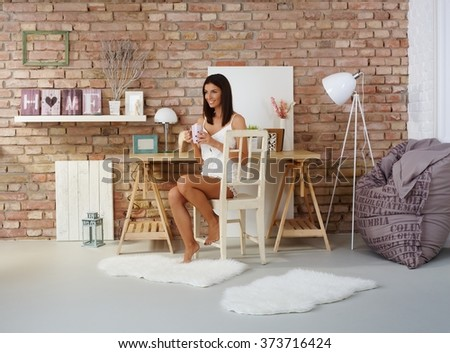 Young attractive woman sitting on chair at home, drinking tea, smiling happy, looking away. - stock photo