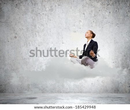 Young attractive woman sitting on cloud and meditating - stock photo