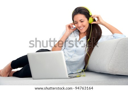 Young attractive woman sitting on couch with laptop and earphones. - stock photo