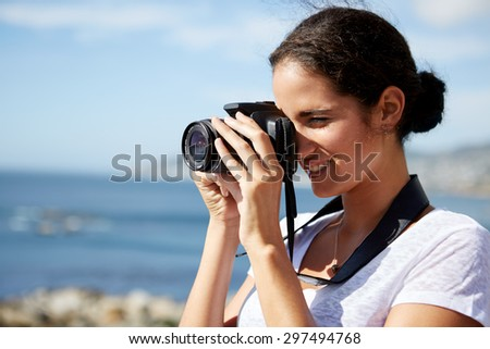 young, attractive woman standing and taking pics of the ocean using a digital camera