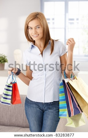 Young attractive woman standing in living room with shopping bags, smiling.?