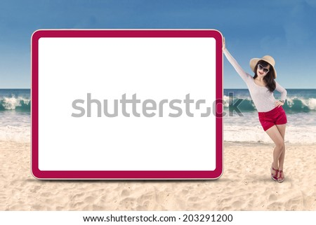 Young attractive woman standing next to copyspace. shot on the beach - stock photo