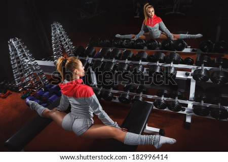 Young attractive woman stretching her middle splits in gym club - stock photo