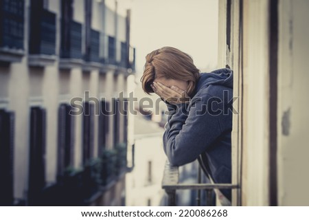 young attractive woman suffering depression and crying in stress outdoors at home balcony terrace window in pain and grief feeling sad and desperate in urban background - stock photo