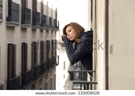 young attractive woman suffering depression and stress at the home balcony window terrace in pain and grief feeling sad and desperate in city urban background - stock photo