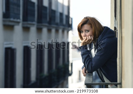 young attractive woman suffering depression and stress outdoors at the balcony window in pain and grief feeling sad and desperate in urban background