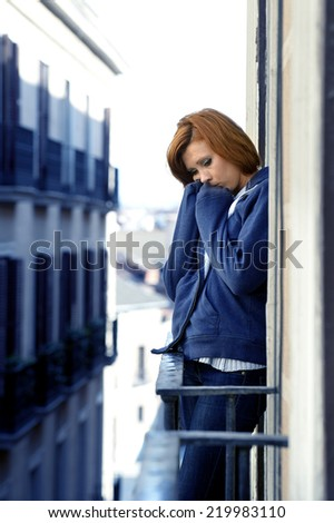 young attractive woman suffering depression and stress outdoors at the balcony window in pain and grief feeling sad and desperate in urban background - stock photo