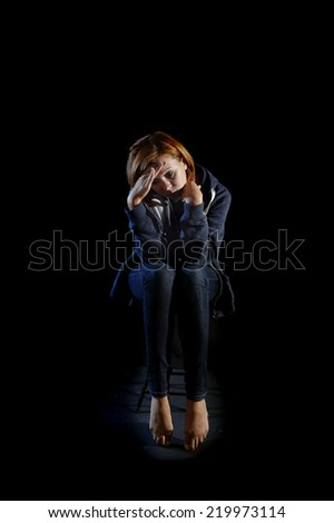 young attractive woman suffering depression and stress sitting alone in pain and grief feeling sad and desperate isolated on black background - stock photo
