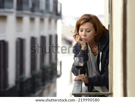 young attractive woman suffering depression and stress smoking drinking glass of wine at the balcony window in pain and grief feeling sad and desperate in urban background - stock photo