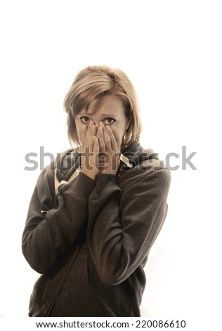 young attractive woman suffering depression and stress standing alone crying in pain and grief against window feeling sad and desperate at home with studio backlight sepia  - stock photo