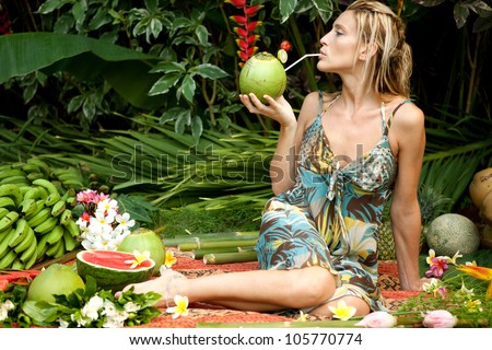 Young attractive woman surrounded by tropical fruits in an exotic garden. - stock photo