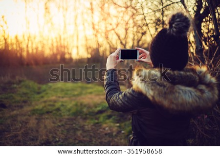 Young attractive woman taking photos with smartphone - stock photo