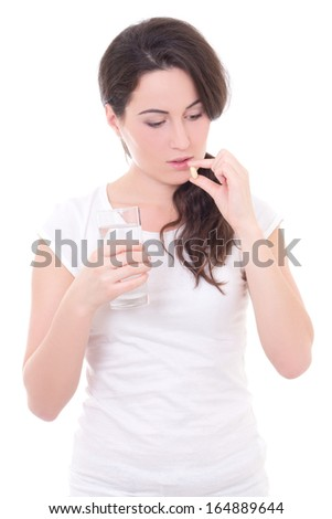 young attractive woman taking pill isolated on white background - stock photo