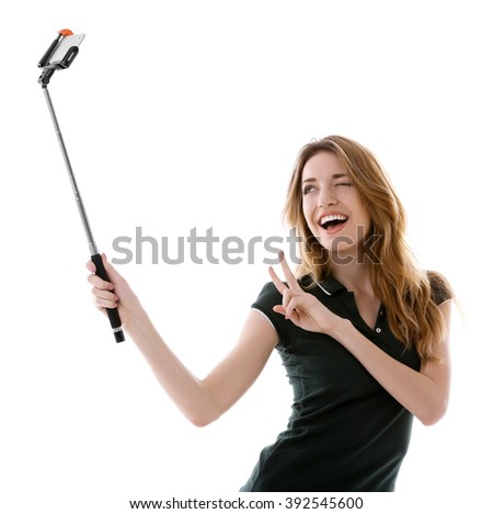 Young attractive woman taking selfie with mobile phone isolated on white - stock photo