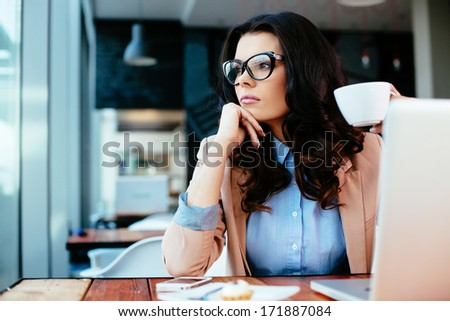 Young attractive woman thinking and holding a cup of coffee - stock photo