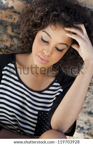 Young attractive woman thoughful on urban background - stock photo