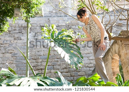 Young attractive woman touching a large green natural leaf while visiting a botanic garden on vacation during a sunny day. - stock photo