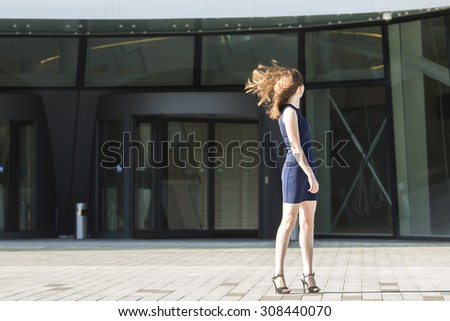 Young attractive woman turning his head waving hair, standing in the background of the business center. - stock photo