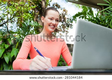 Young attractive woman using her computer - stock photo