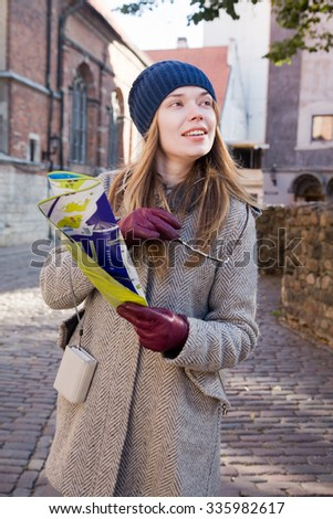 Young attractive woman walking on a city with map in hand
