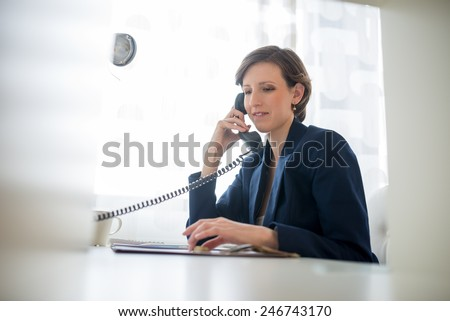 Young attractive woman wearing a blue suit smiling as she listens to the conversation conceptual of a call center or business communication. - stock photo