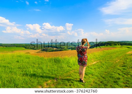 Young attractive woman wearing dress skirt standing in green spring landscape, Burgenland, Austria