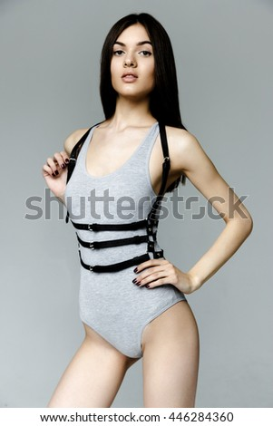 Young attractive woman wearing gray kombidress with leather  belt on gray background - stock photo