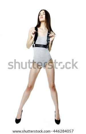 Young attractive woman wearing gray kombidress with leather black belt on white background