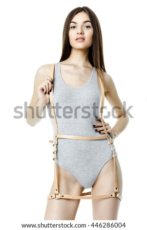 Young attractive woman wearing gray kombidress with leather brown belt on white background - stock photo