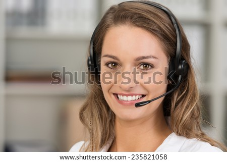 Young attractive woman with a friendly smile wearing a headset for online communication as professional virtual client support or customer service - stock photo