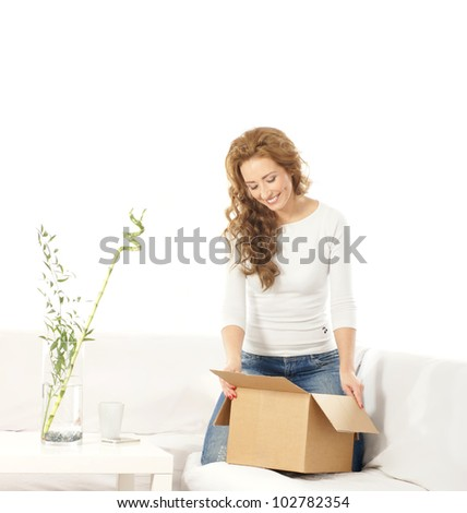 Young attractive woman with a parcel in modern interior - stock photo