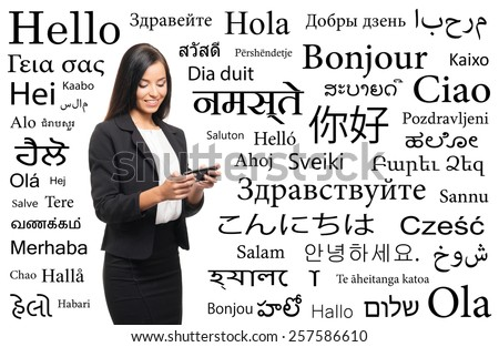 Young attractive woman with a smartphone over the background with a different world languages (language school concept) - stock photo