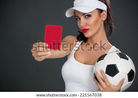 Young attractive woman with a soccer ball showing  red card - stock photo