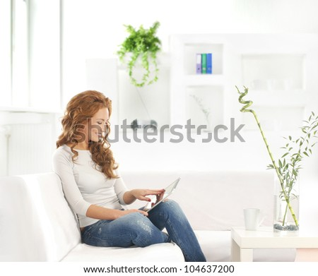 Young attractive woman with a tablet in modern interior - stock photo