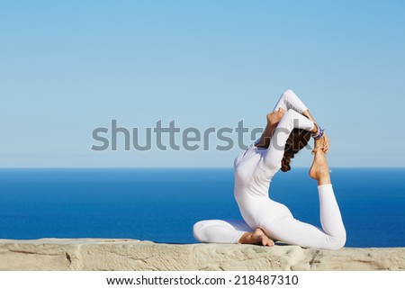 Young attractive woman with beautiful body engage yoga at high altitude on beautiful ocean background,yoga at sunny day performing by beautiful healthy woman in white clothes,felling healthy with yoga - stock photo
