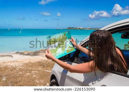Young attractive woman with great map of island in the car - stock photo