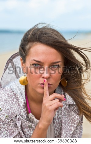 Young attractive woman with his finger around his lips. Portrait of a Woman. Outdoor, summer.