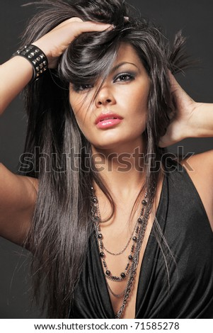 Young attractive woman with long black hair on black background. - stock photo