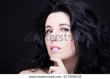 Young attractive woman with long black hair on dark background.
