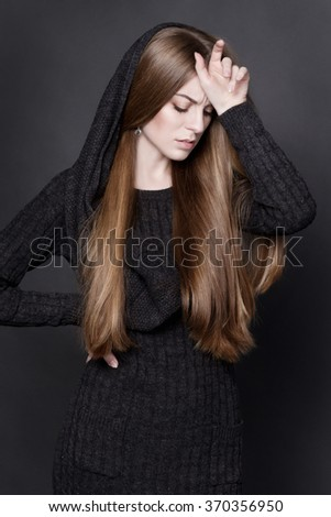 Young attractive woman with long, gorgeous dark blond hair. She is dressed in warm gray knit dress with a hood. She looks tired. Her gesture expresses serious thoughts and despair. - stock photo