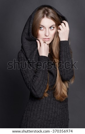 Young attractive woman with long, gorgeous dark blond hair. She is dressed in warm gray knit dress with a hood. She is concerned. She looks around and hides her face. - stock photo
