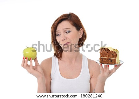 Young Attractive Woman with red hair holding Apple and Cake in hands in a healthy versus tasty Dessert Choice isolated on White background  - stock photo