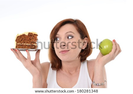 Young Attractive Woman with red hair holding Apple and Cake in hands in a healthy versus tasty Dessert Choice isolated on White background