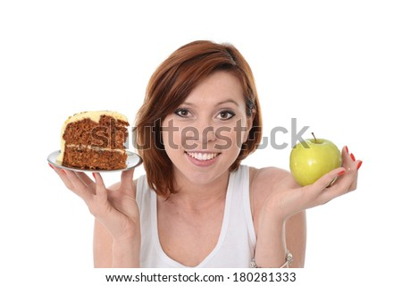 Young Attractive Woman with red hair smiling and holding Apple and Cake in hands in a healthy versus tasty Dessert Choice isolated on White background